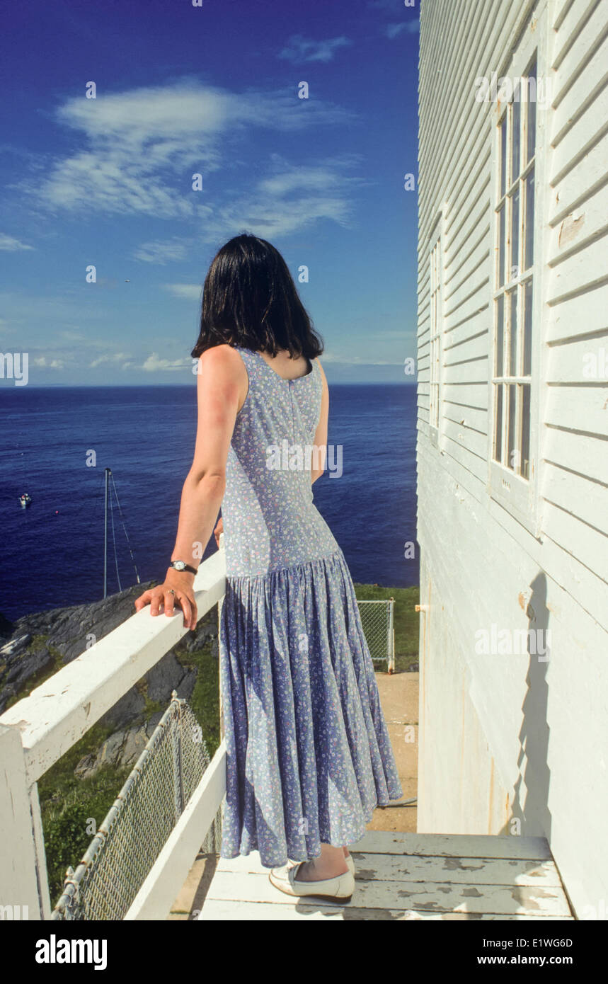 Young lady looking out to sea, Lighthouse, Cape St. Francis, Newfoundland, Canada, Model release - Stock Image