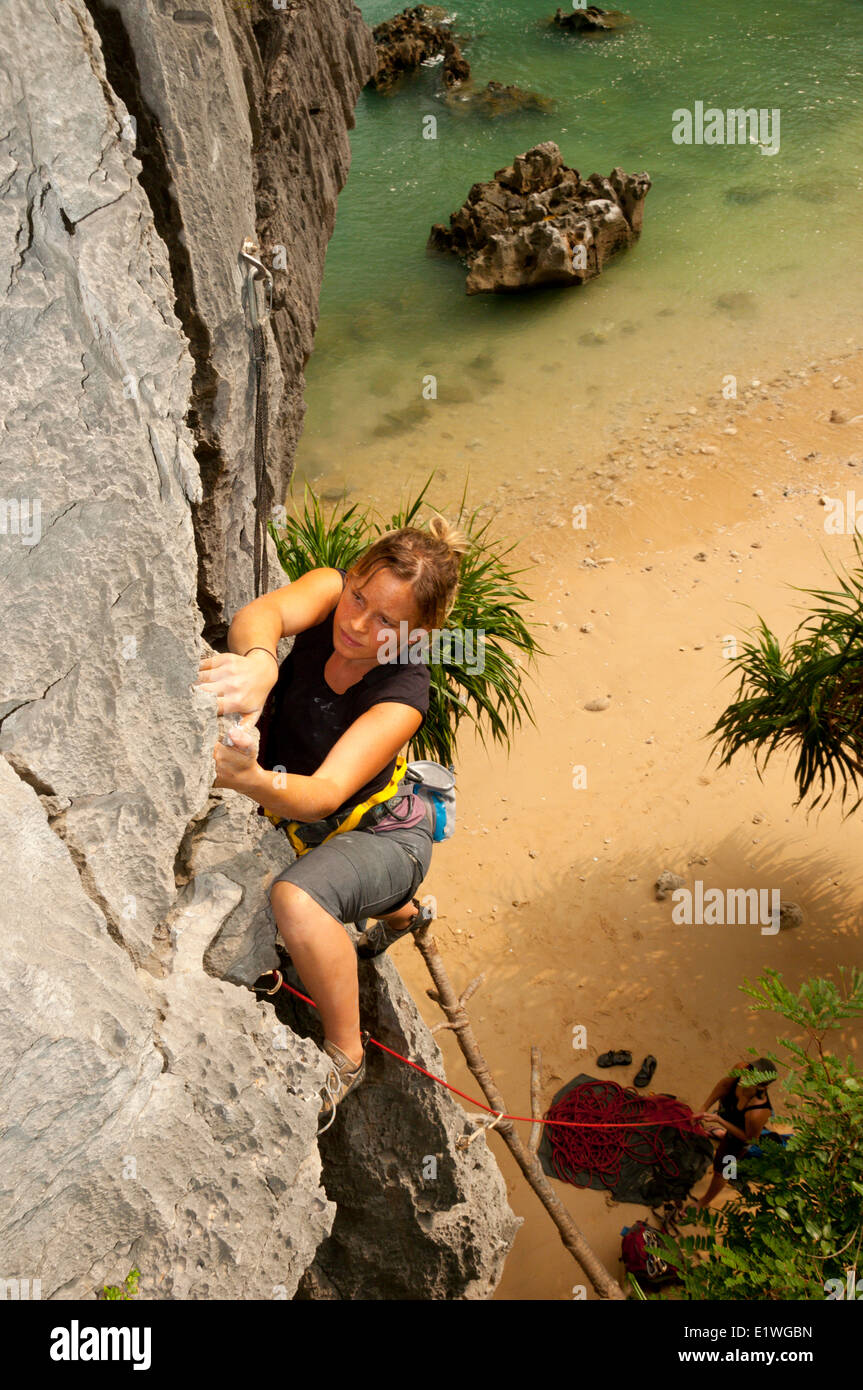 A young woman rock climbing in Lan Ha Bay, Vietnam - Stock Image