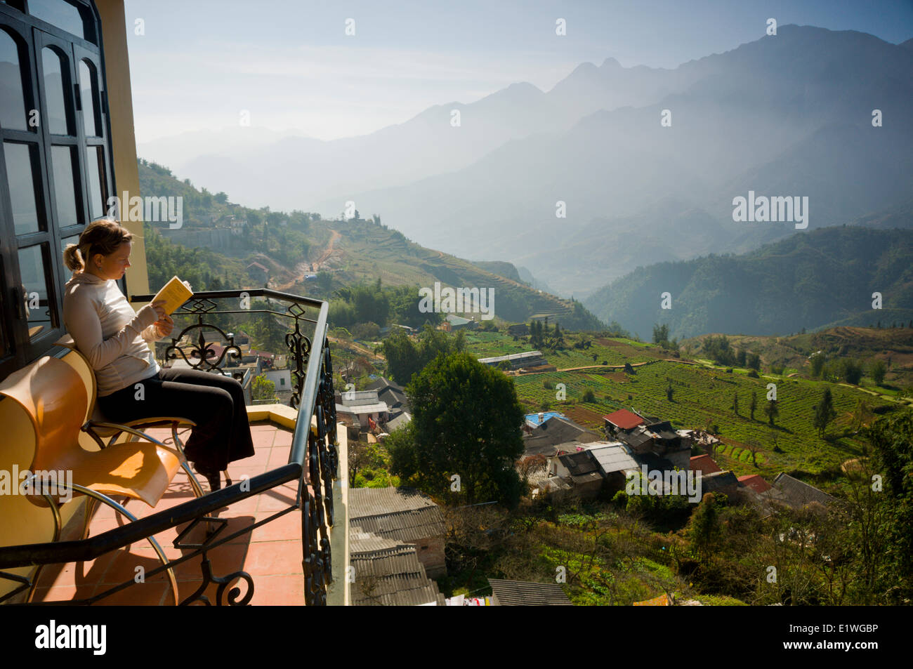 A woman reads on her balcony at a hotel in Sapa, Vietnam - Stock Image