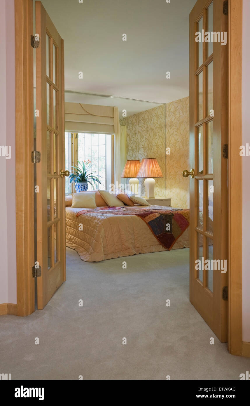 View the master bedroom through opened french doors inside a ...