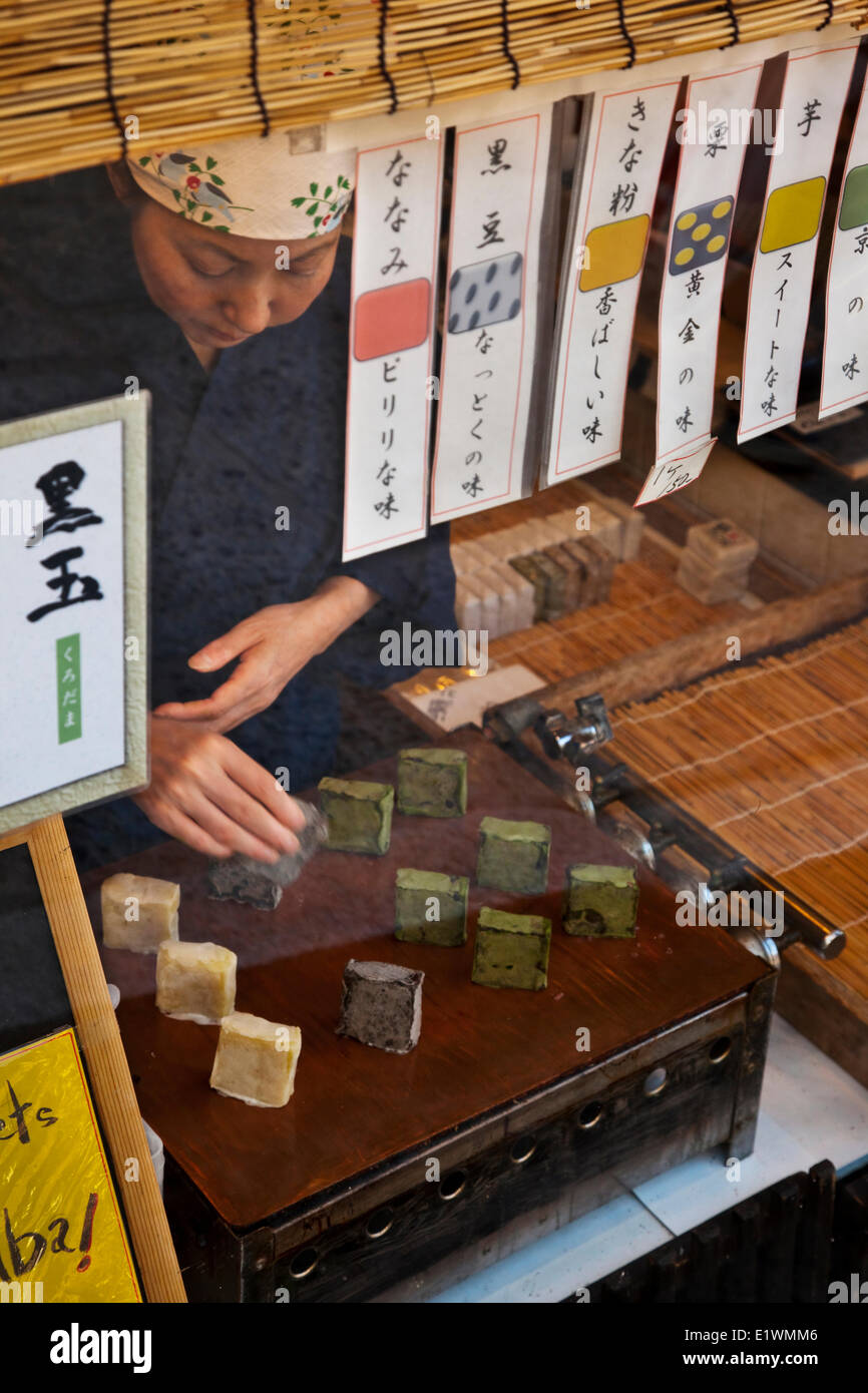 Shopkeeper placing wagashi confectionery on her storefront window display. Ninenzata Street, in Kyoto, Japan. - Stock Image