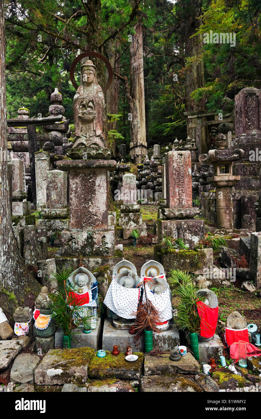 Grouping tombstones small statuettes drapped with red or white bibs that represent Jizo the bodhisattva that according - Stock Image