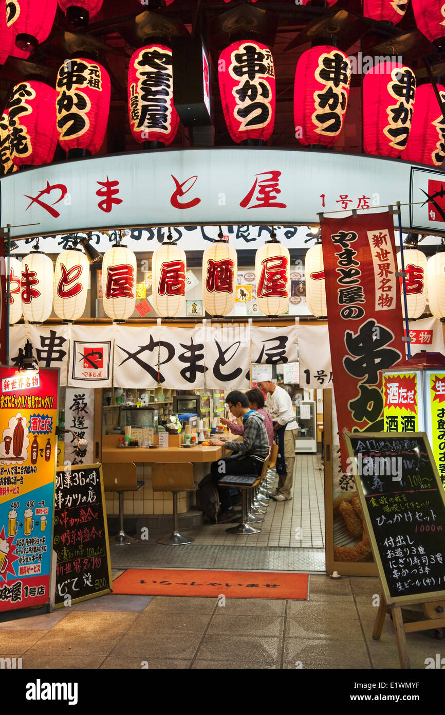 Small restaurant with abundant signage in Osaka's Shinsekai district. The neighbourhood was created in 1912 - Stock Image