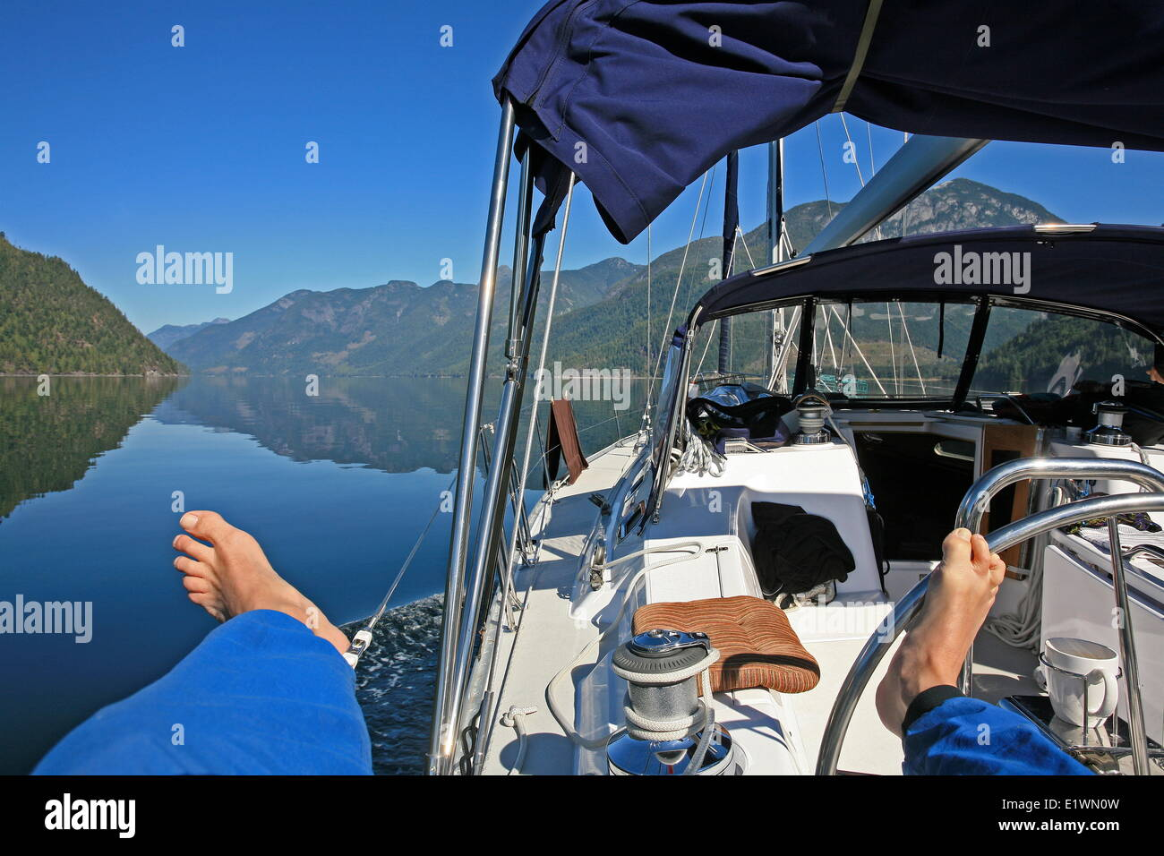 motoring through Desolation Sound, British Columbia, with feet on steering wheel and relaxing, Darrel Giesbrecht - Stock Image