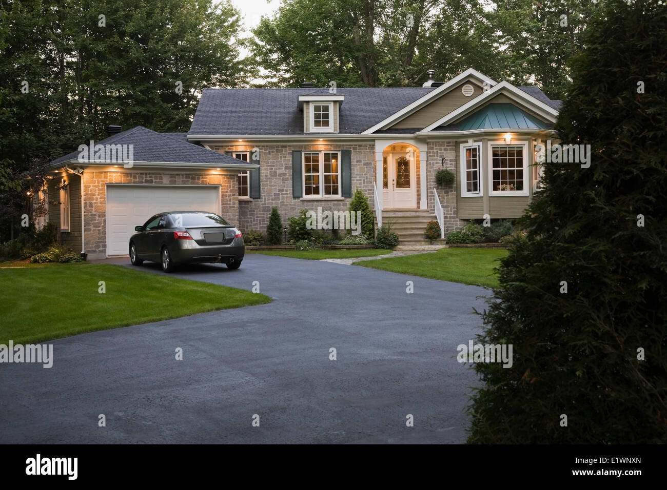 Brown beige gray stone residential home landscaped front yard illuminated at dusk Quebec Canada. This image is property - Stock Image