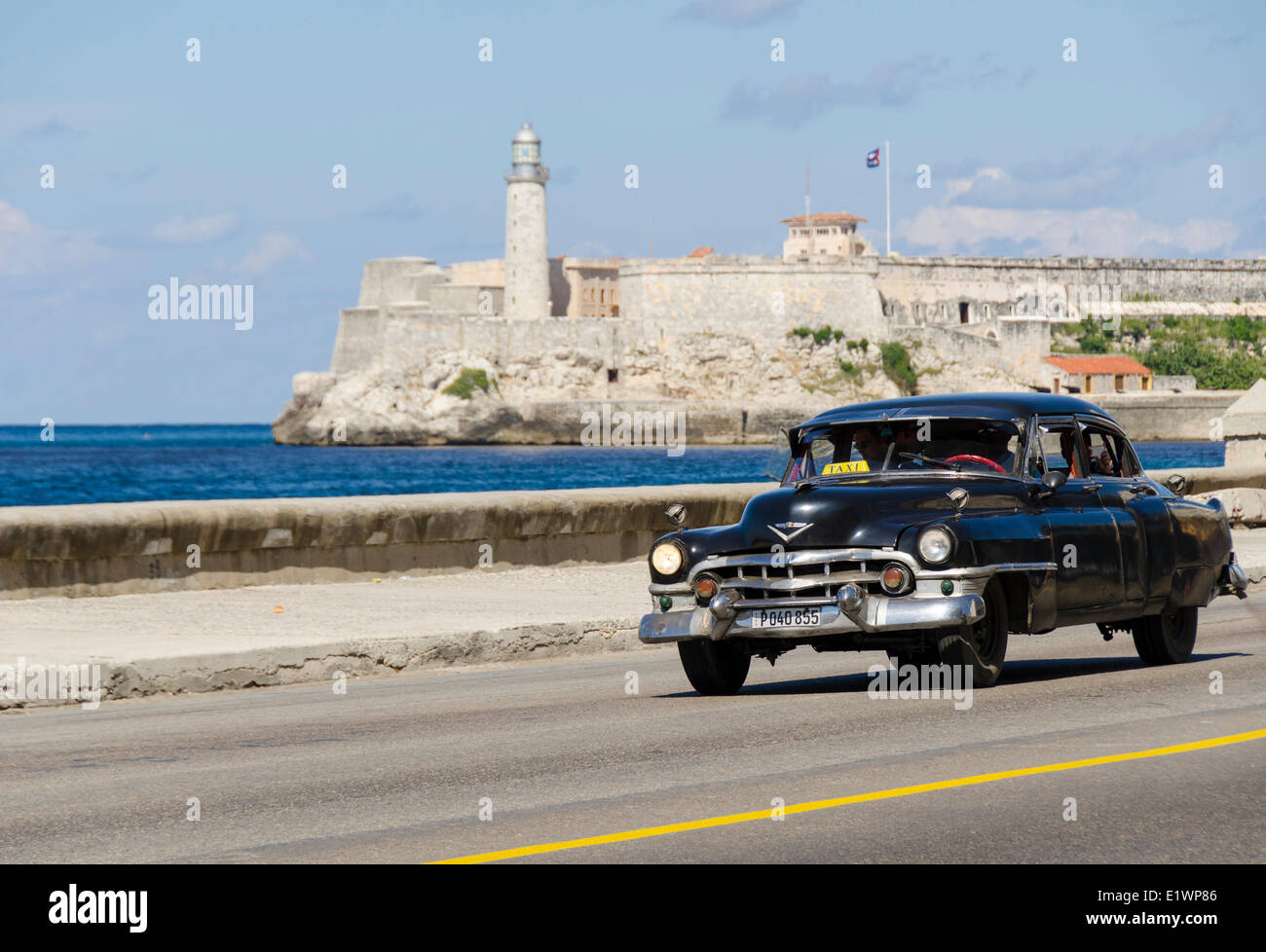 Vintage american cars alomg the Malecon, behind is Morro Castle, a picturesque fortress guarding the entrance to Stock Photo