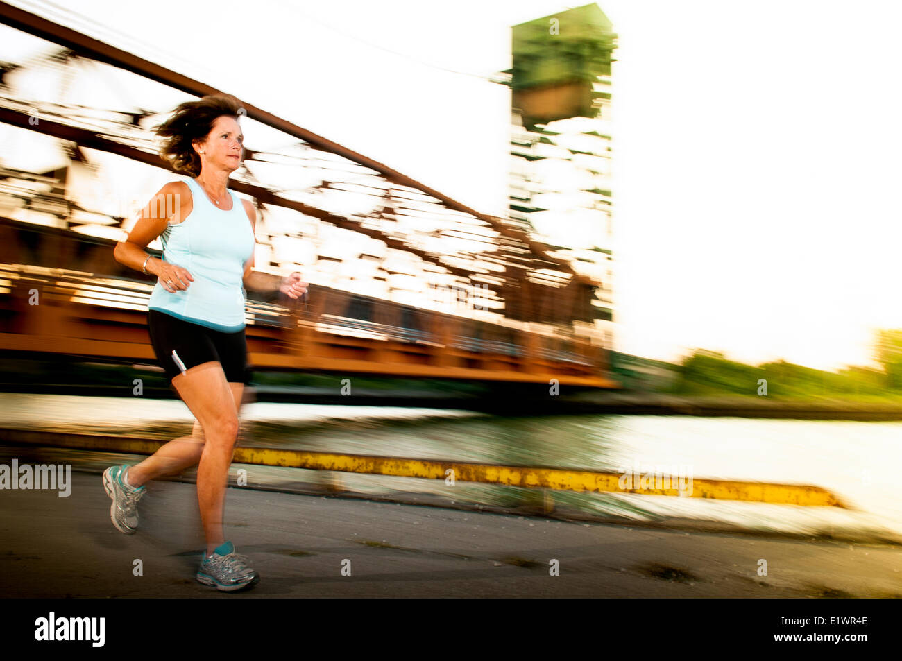 Attractive woman in her 50's jogging on an urban trail. - Stock Image