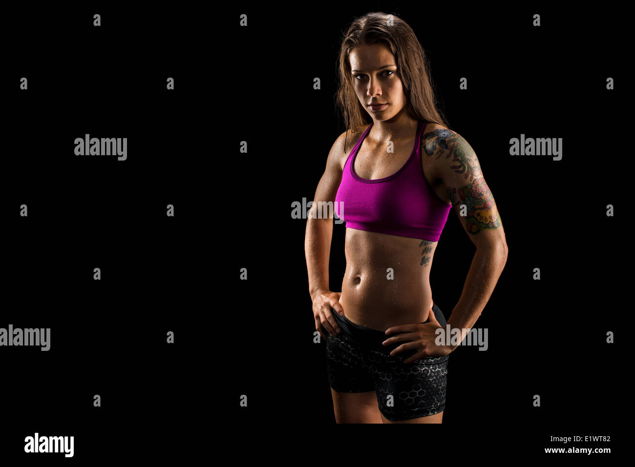 Healthy muscular female athlete wearing athletic wear - Stock Image