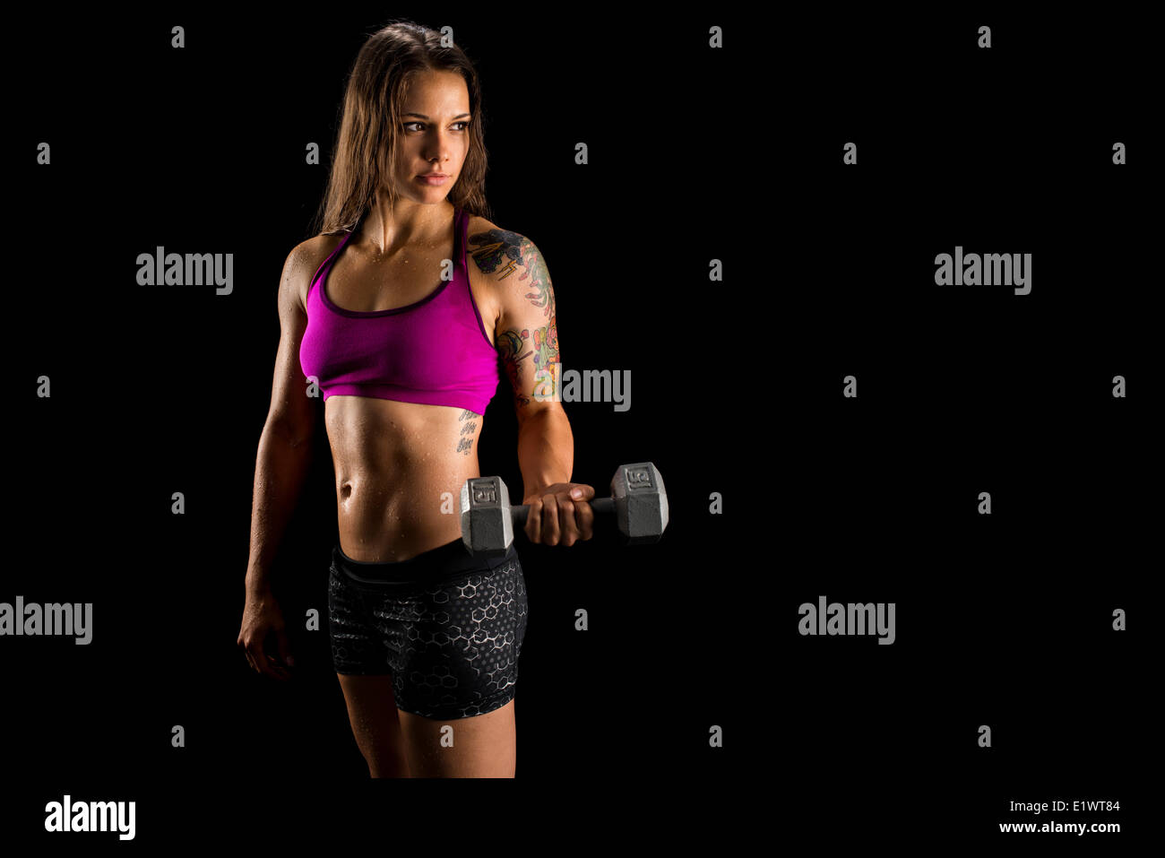 Fit athletic woman working out with dumbell - Stock Image