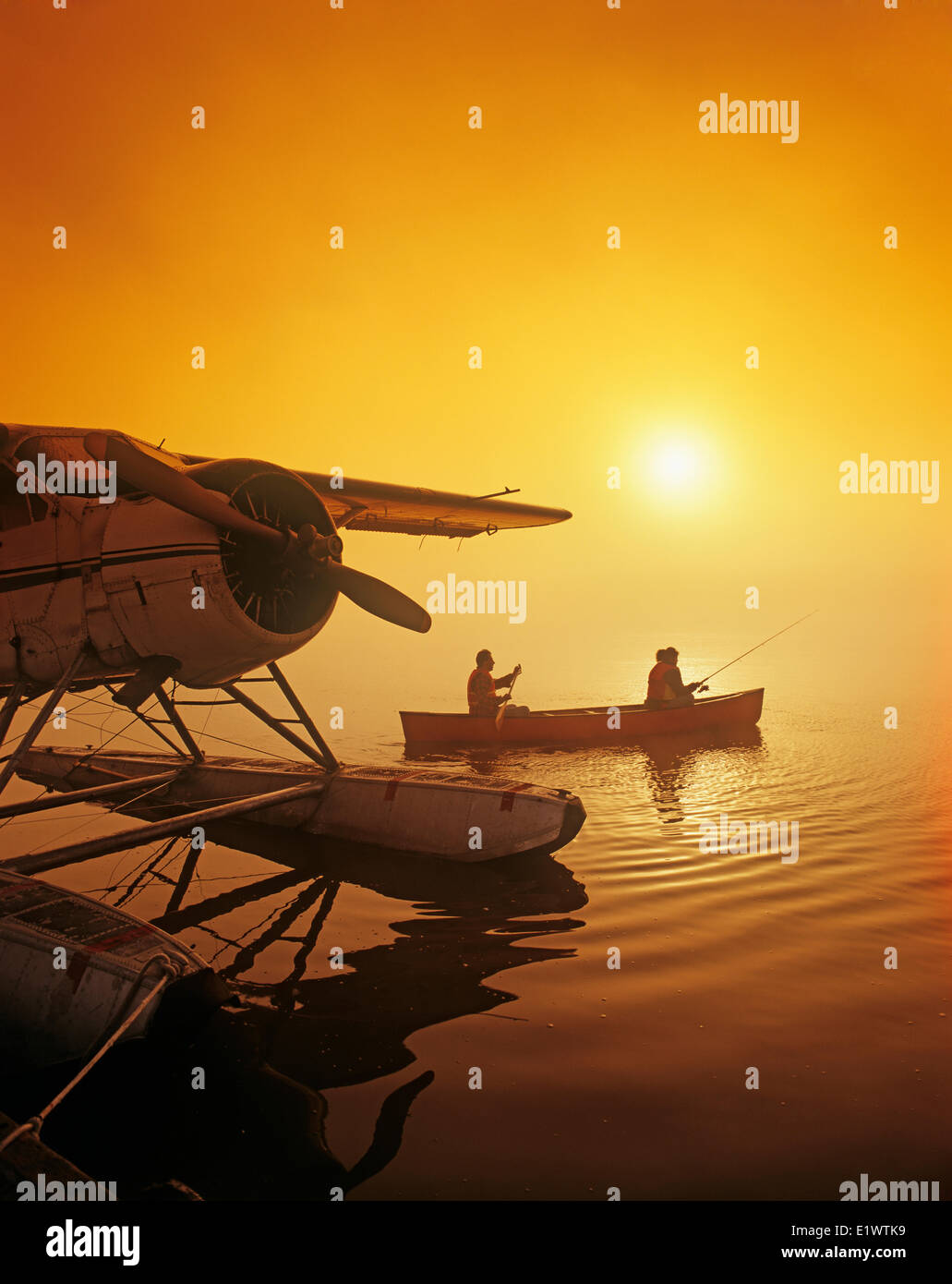 couple canoeing and fishing next to float plane dock, Manitoba, Canada - Stock Image