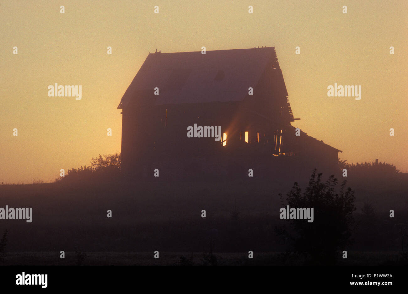 Barn appears lite as sun rises behind the building. Many old structures in this area are preserved as reminders - Stock Image