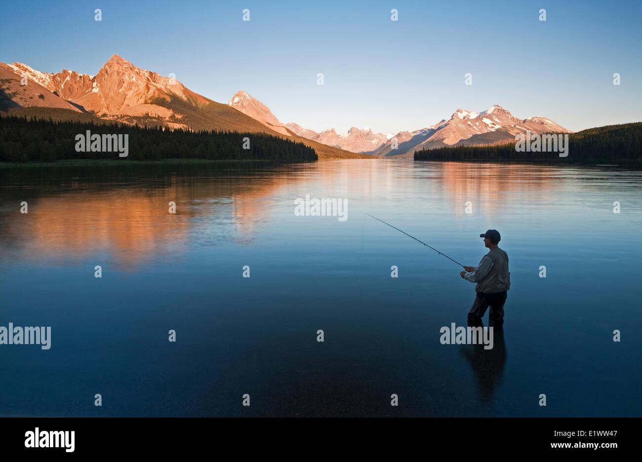 Middle age male fly fishing on Maligne Lake, Jasper National Park, Alberta, Canada. Stock Photo