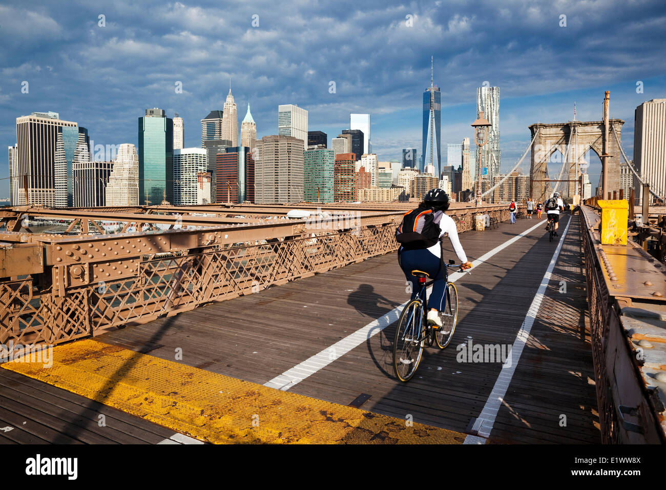 Spanning the East River between Manhattan and Brooklyn, the Brooklyn Bridge features a wide walkway above a six - Stock Image