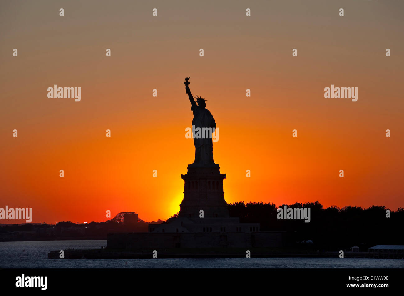 Silhouetted Statue of Liberty photographed against the setting sun. Liberty Island, New York, U.S.A. - Stock Image