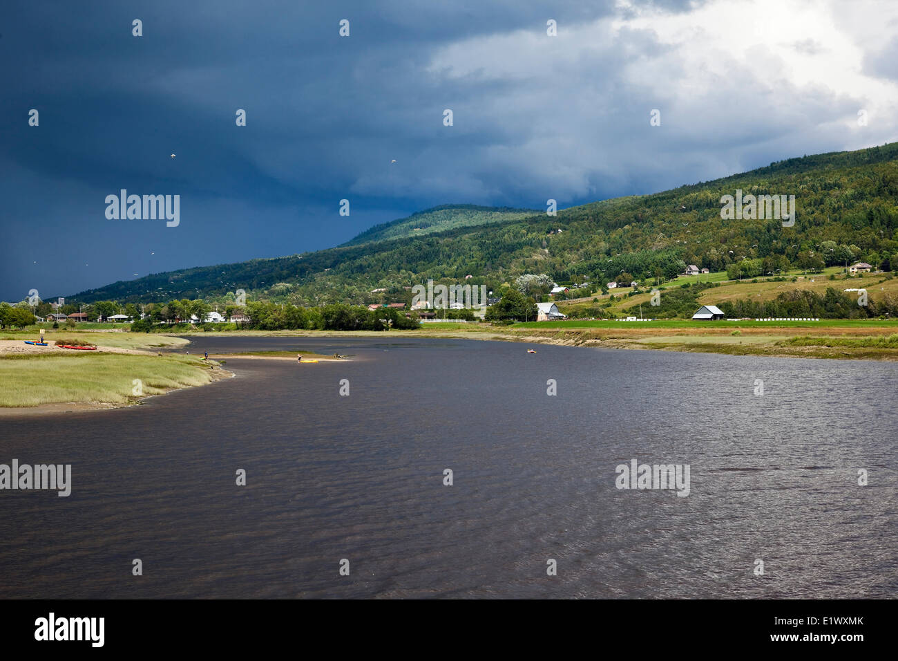 Dark clouds advancing over Riviere du Gouffre (Gouffre River) at the point where it empties into the St. Lawrence - Stock Image
