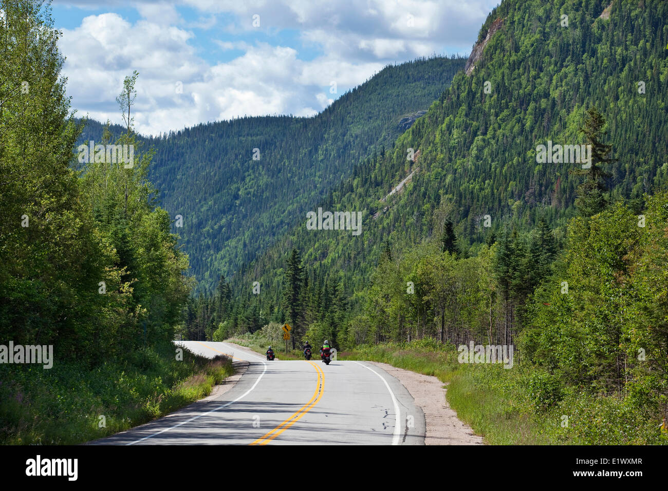 Motocyclists touring on a road that cuts through a mountain range in ...