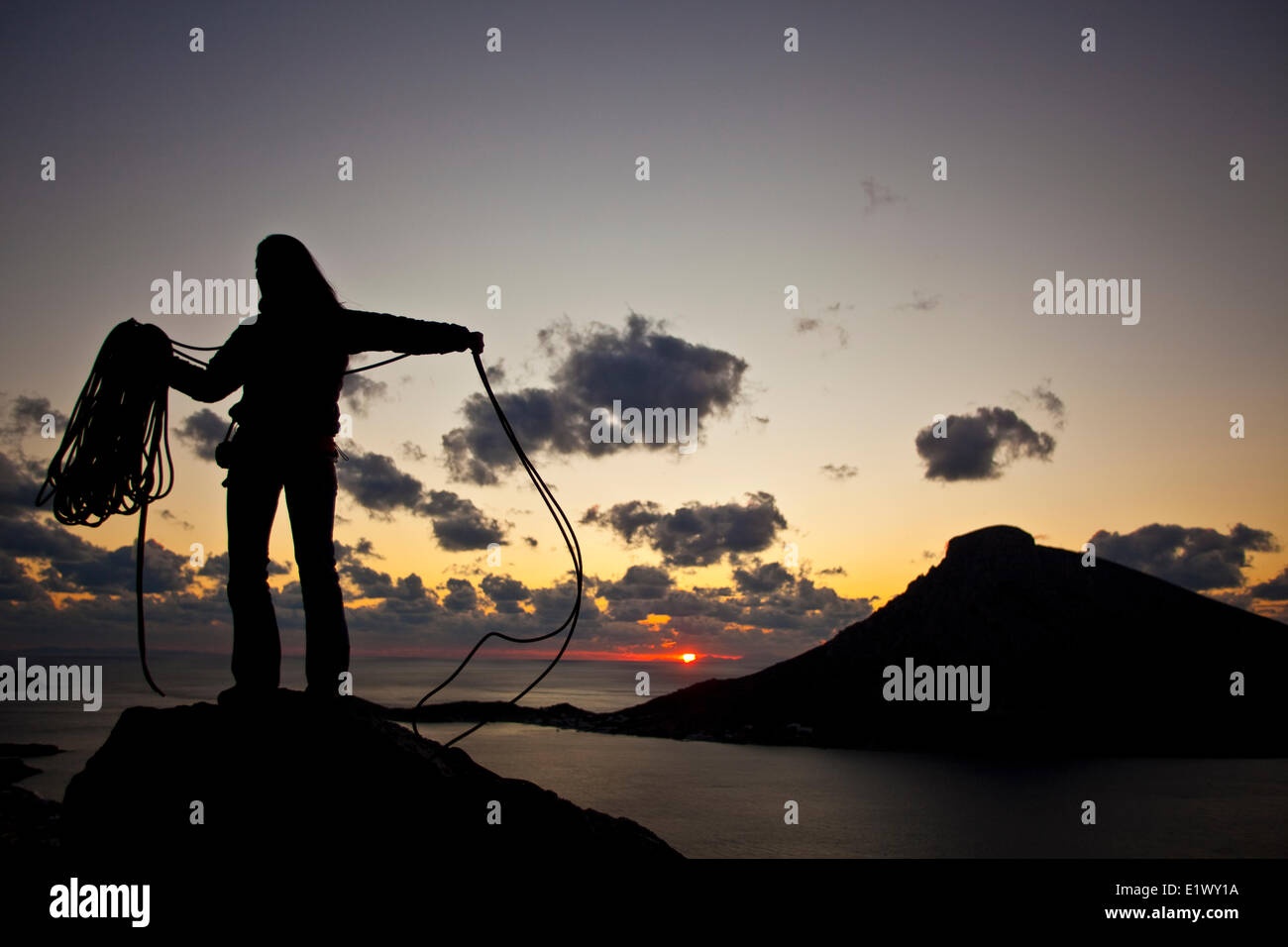 A young woman coiling the rope after a day of climbing in Kalymnos, Greece - Stock Image