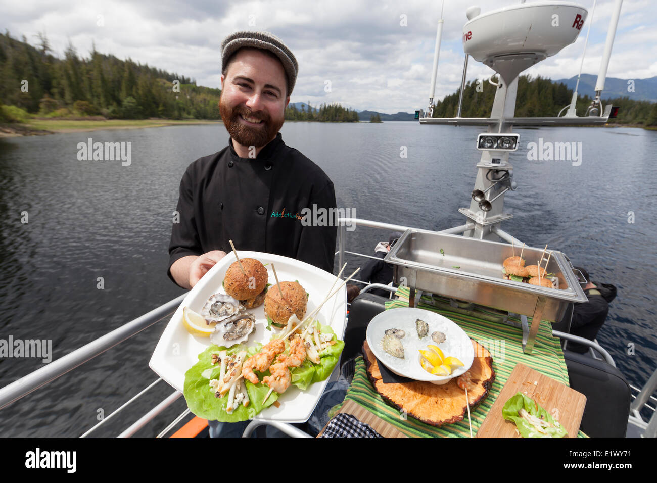 A smiling chef aboard a West Coast Safari tour boat presents a fresh bounty food for passengers to eat.  Browning - Stock Image