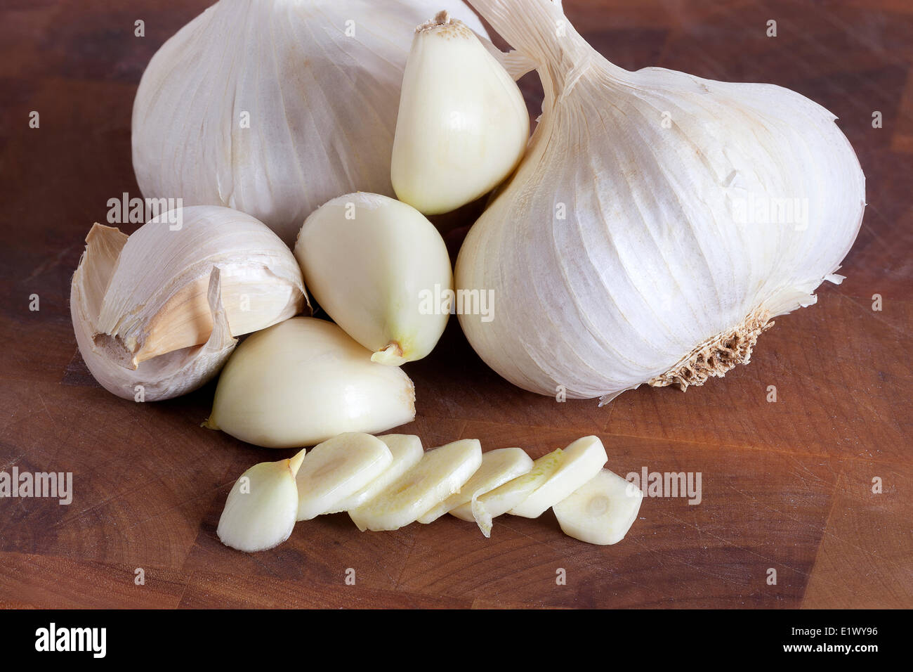 Sliced and whole garlic cloves on a wooden cutting board - Stock Image