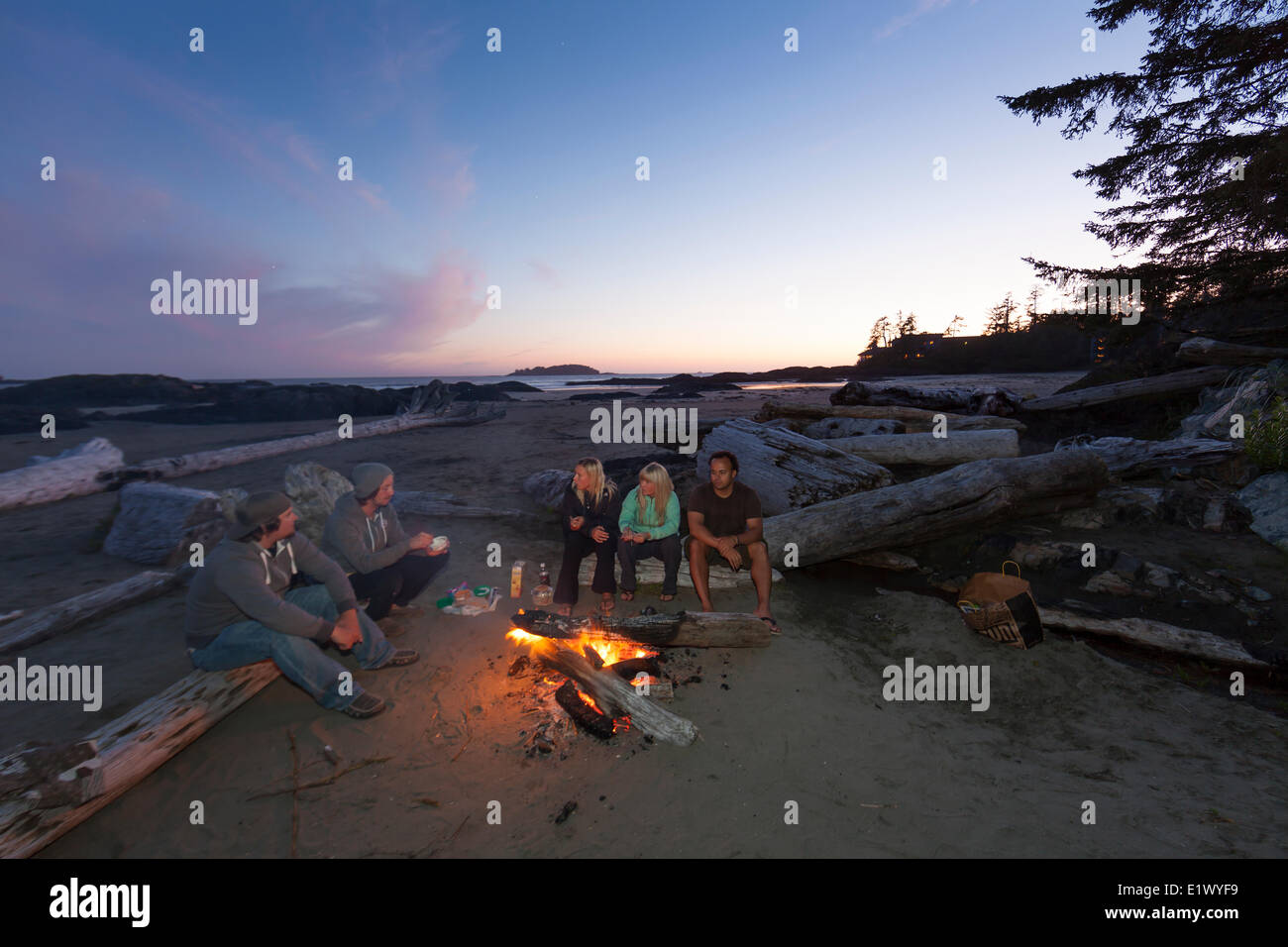 Friends gather around a fire for snacks conversation on Chesterman Beach.  Tofino Vancouver Island British Columbia - Stock Image