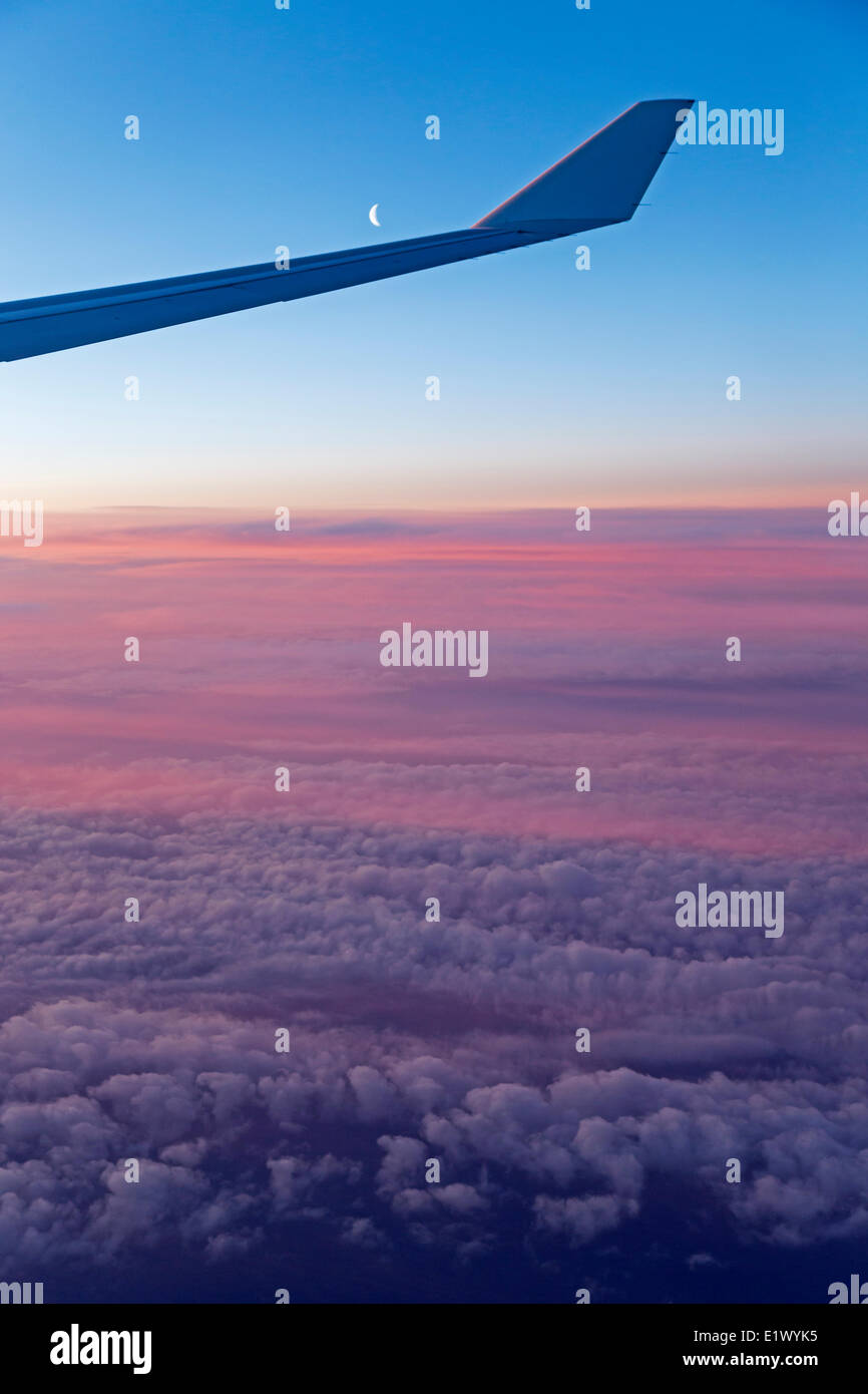 Aerial, clouds, flying, new moon, sunrise, airplane wing, - Stock Image