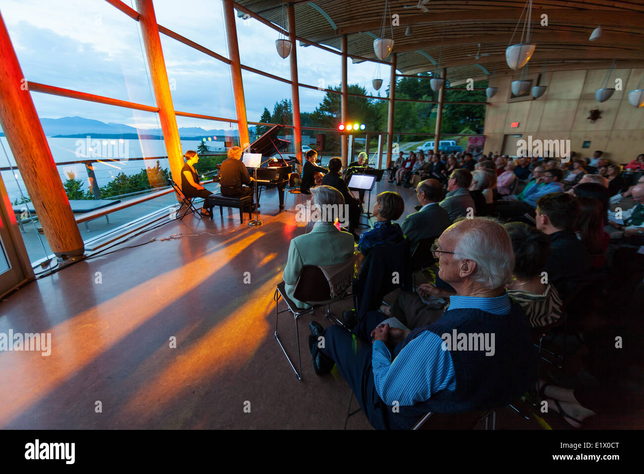 Guests listen to music at the annual Music By The Sea summer concert held in the spectacular Rix Centre overlooking - Stock Image