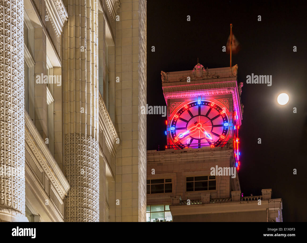 Vancouver Block Clock Tower and Hudson's Bay Building at night with 3/4 moon, Vancouver, British Columbia, Canada - Stock Image