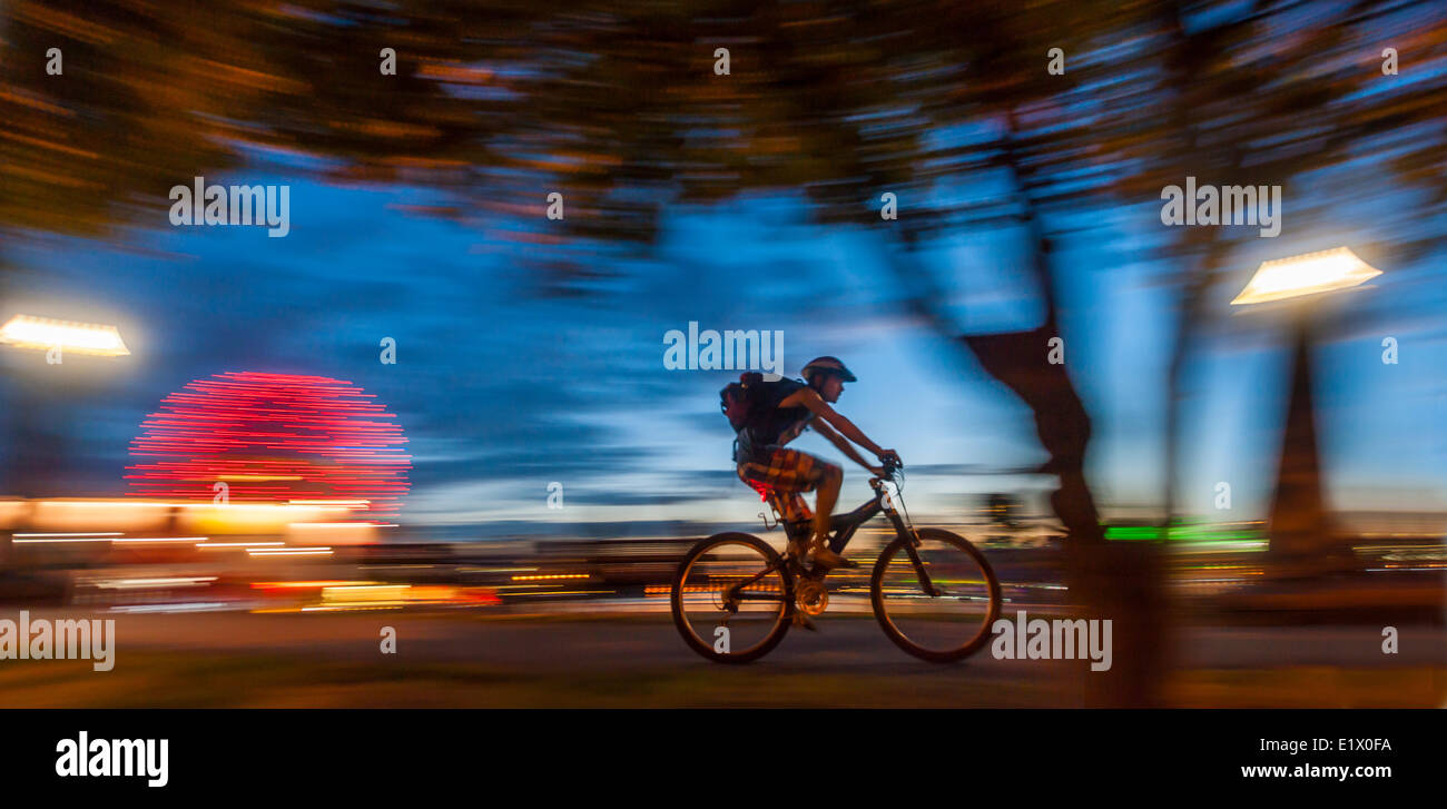 Bicyclist and Science World at dusk. - Stock Image