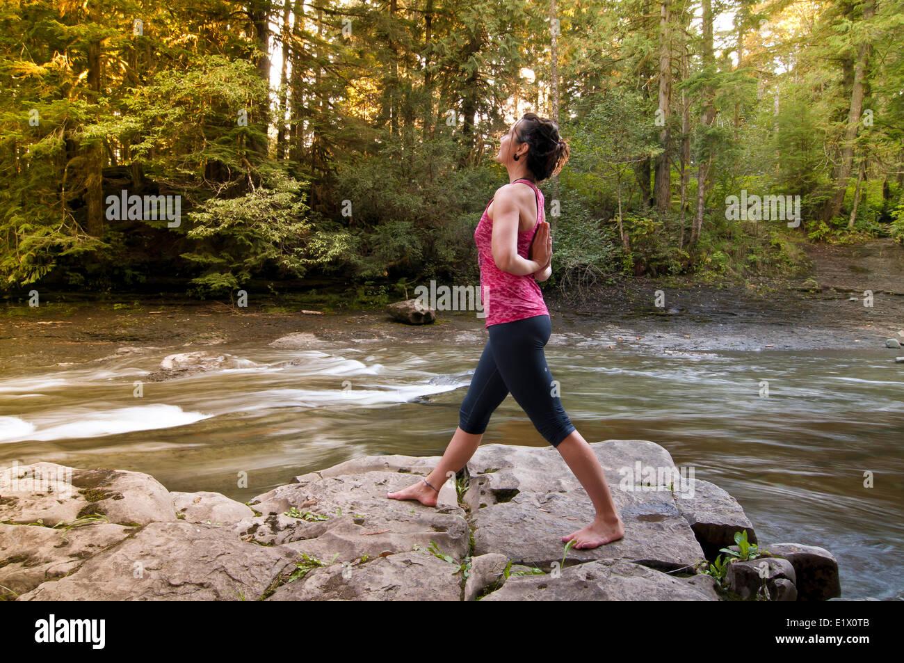 A woman hodling a reverse prayer yoga pose, Courtenay British Columbia, Canada - Stock Image