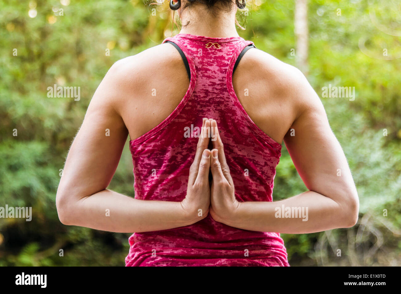A girl in a pink tank hodling a reverse prayer yoga pose, Courtenay British Columbia, Canada - Stock Image