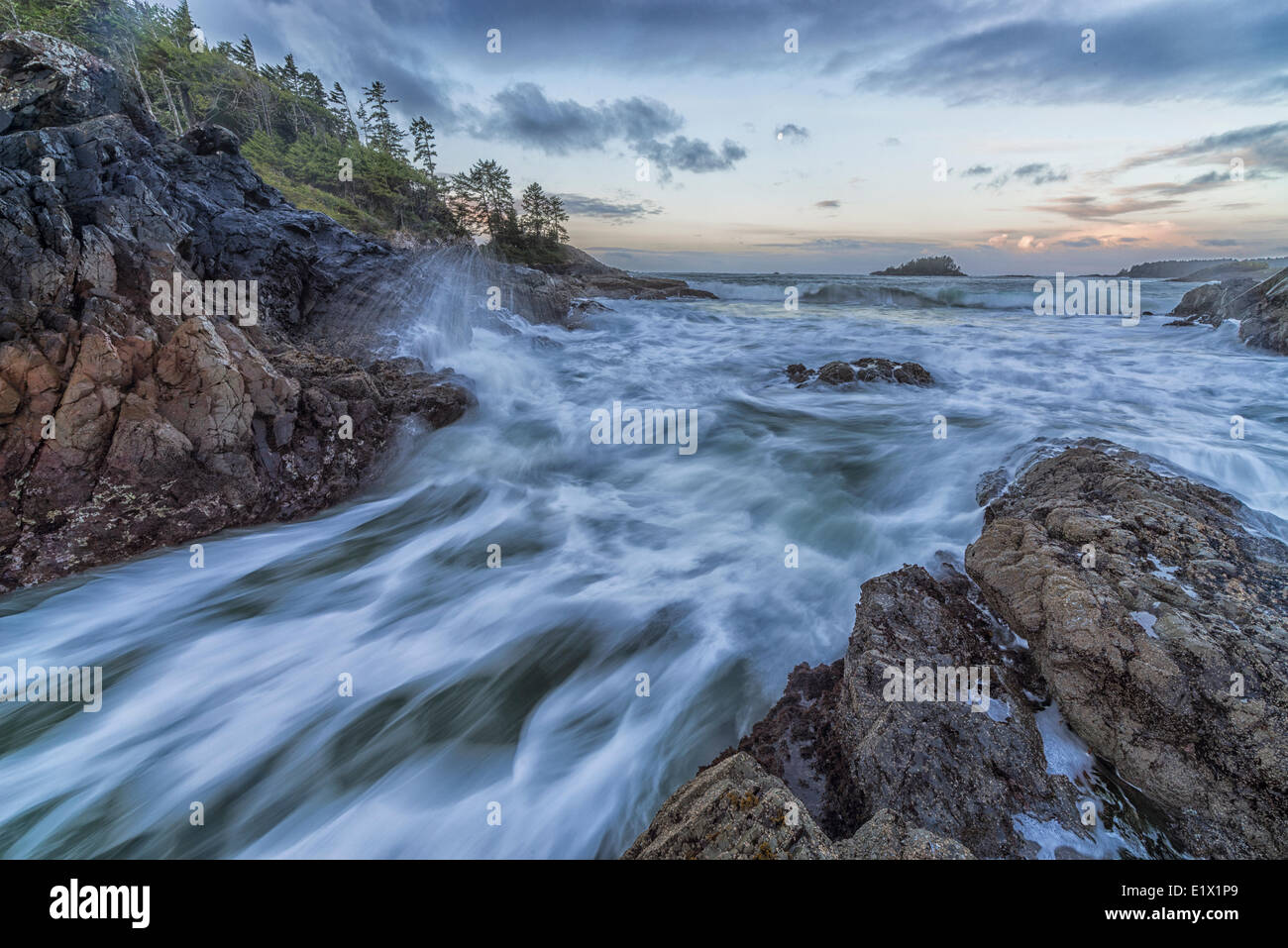 Dawn breaks over Crystal Cove Tofino as the tide rises to cover the rocks large waves crash against the shoreline - Stock Image