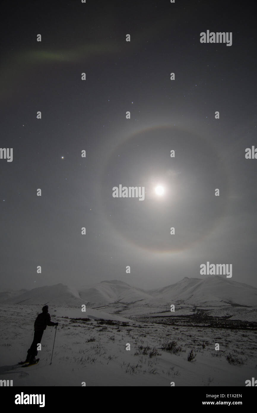 Halo around the moon as a person watches while snowshoeing along the Dempster Highway, Yukon. - Stock Image