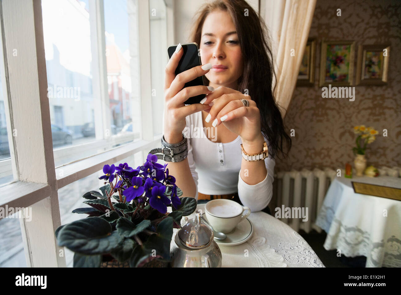 Young woman using smart phone at cafe table Stock Photo