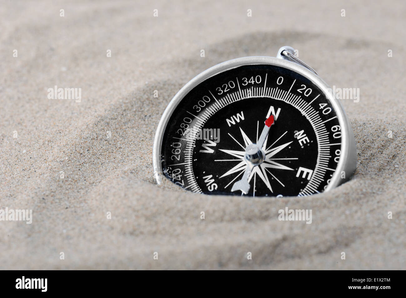 a compass part buried in sand with needle pointing north - Stock Image