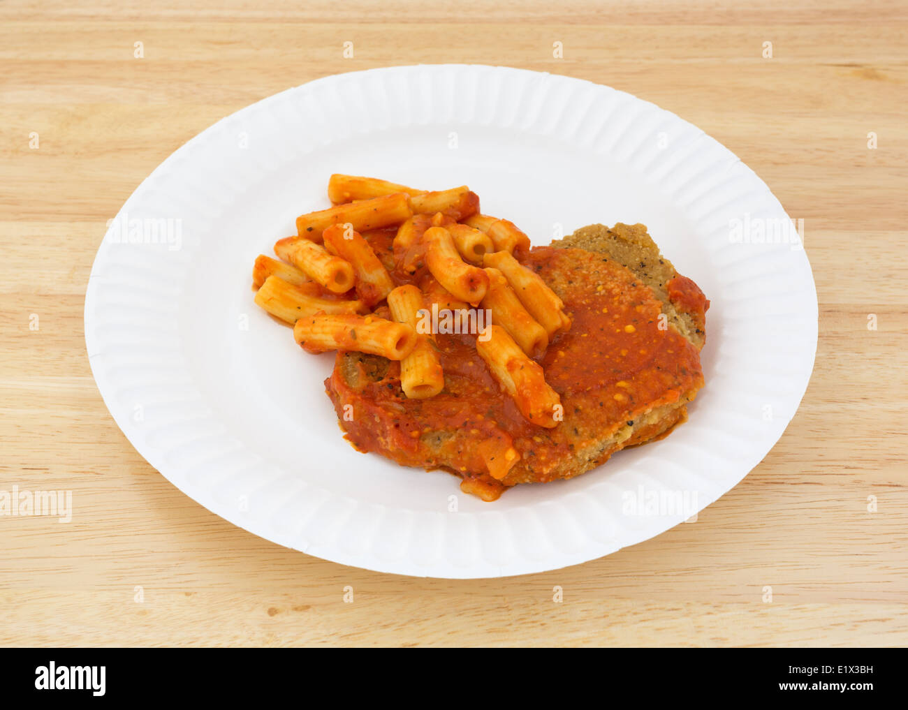 A cooked TV dinner of breaded chicken with tomato sauce and pasta on a paper plate atop a wood tabletop. - Stock Image