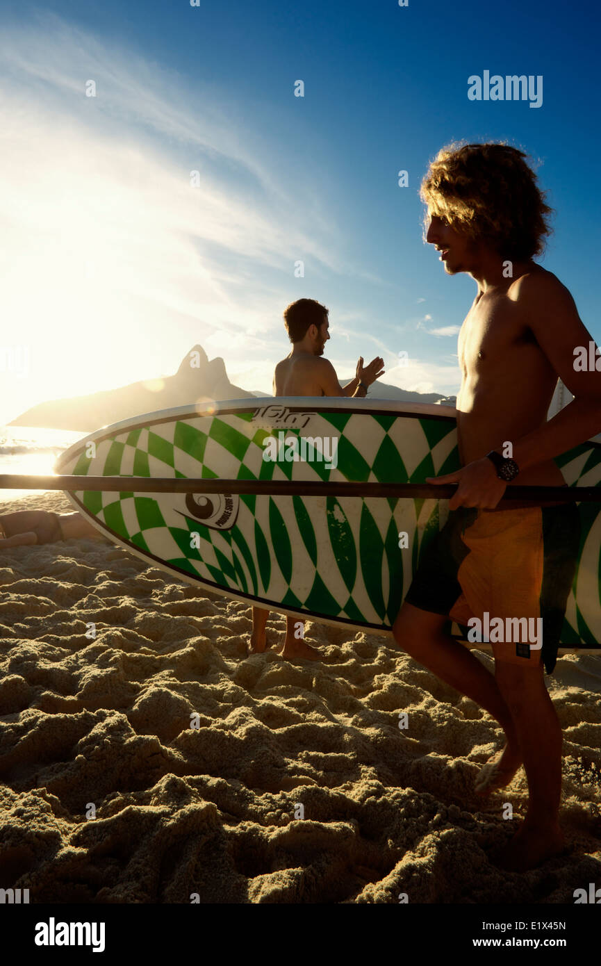 RIO DE JANEIRO, BRAZIL - JANUARY 18, 2014: Young Brazilian surfer walks with surfboard toward the waves on Ipanema - Stock Image