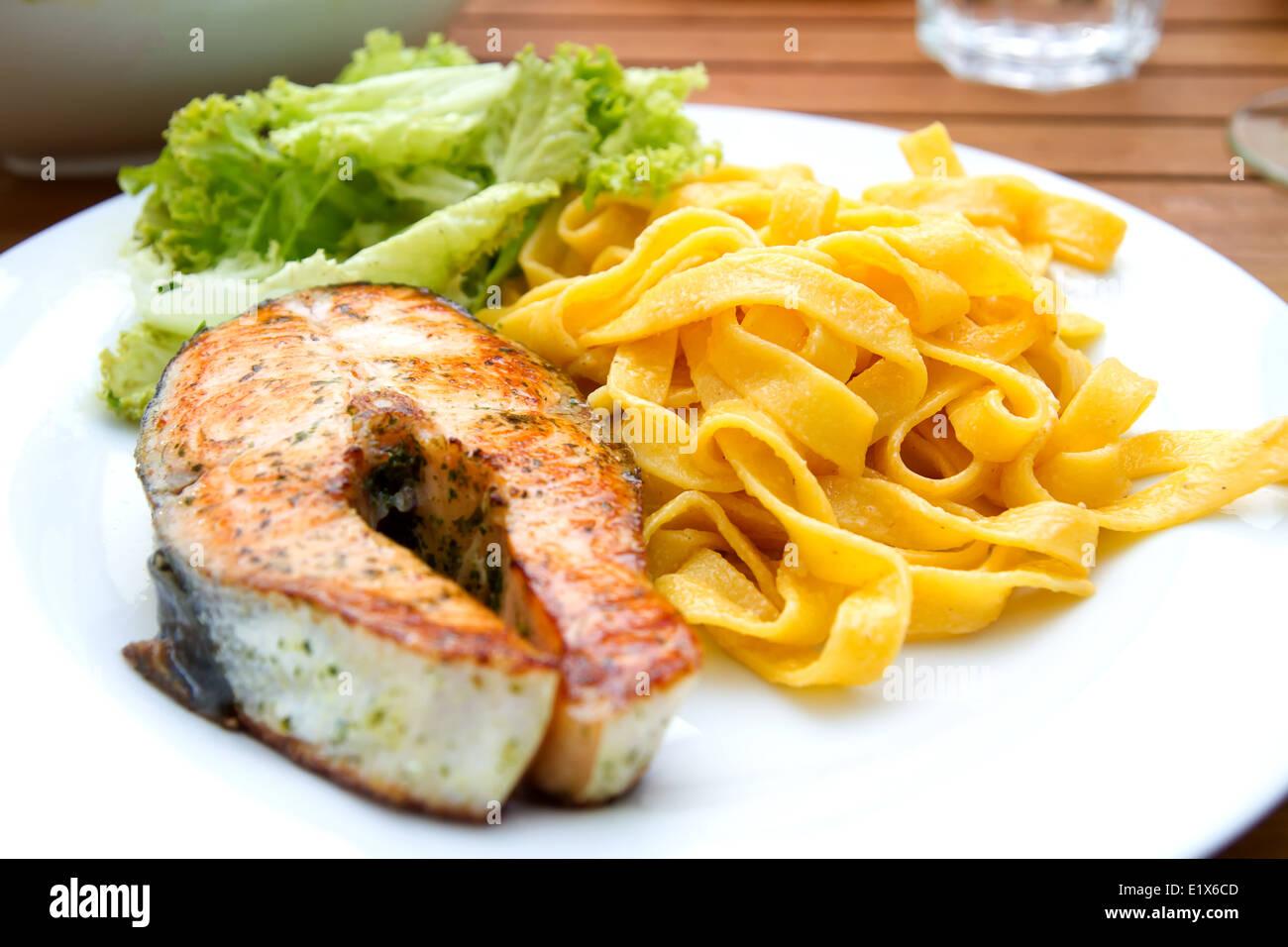 Lachs mit Pasta und Salat - Stock Image