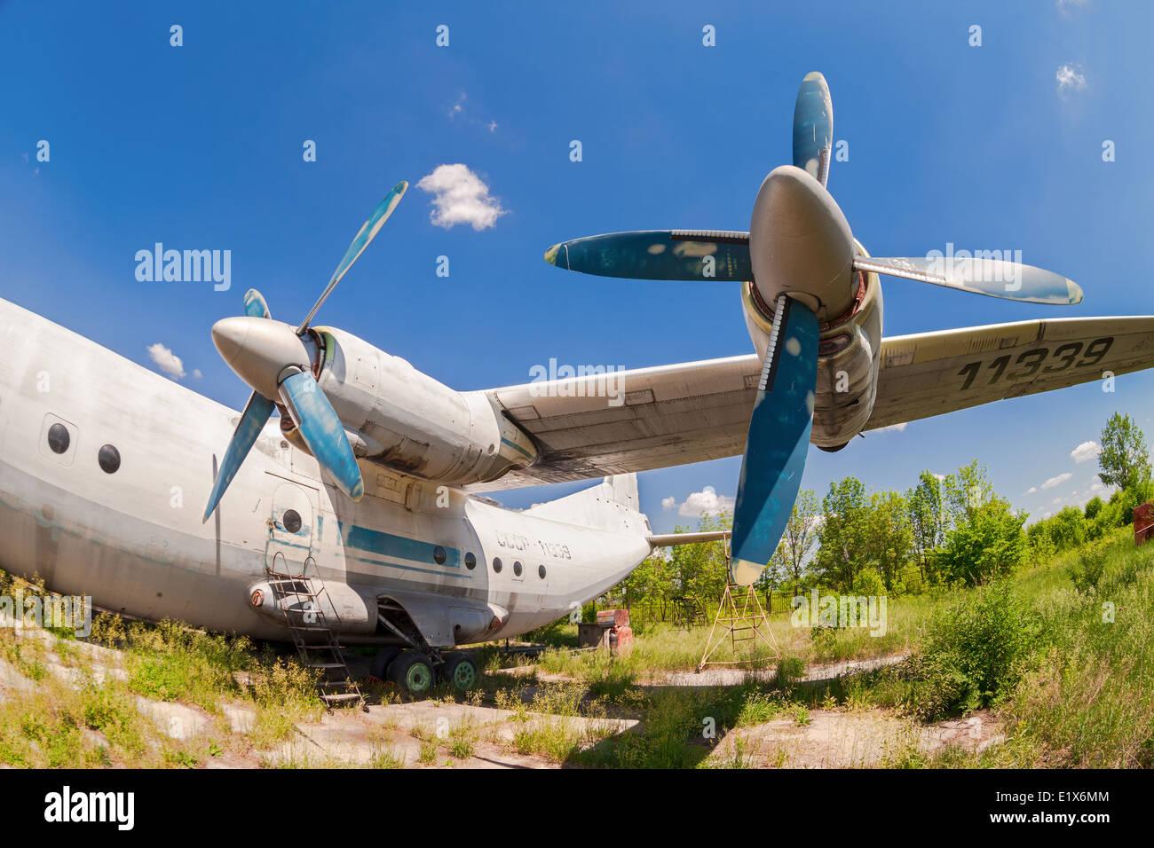 Old russian aircraft An-12 at an abandoned aerodrome - Stock Image