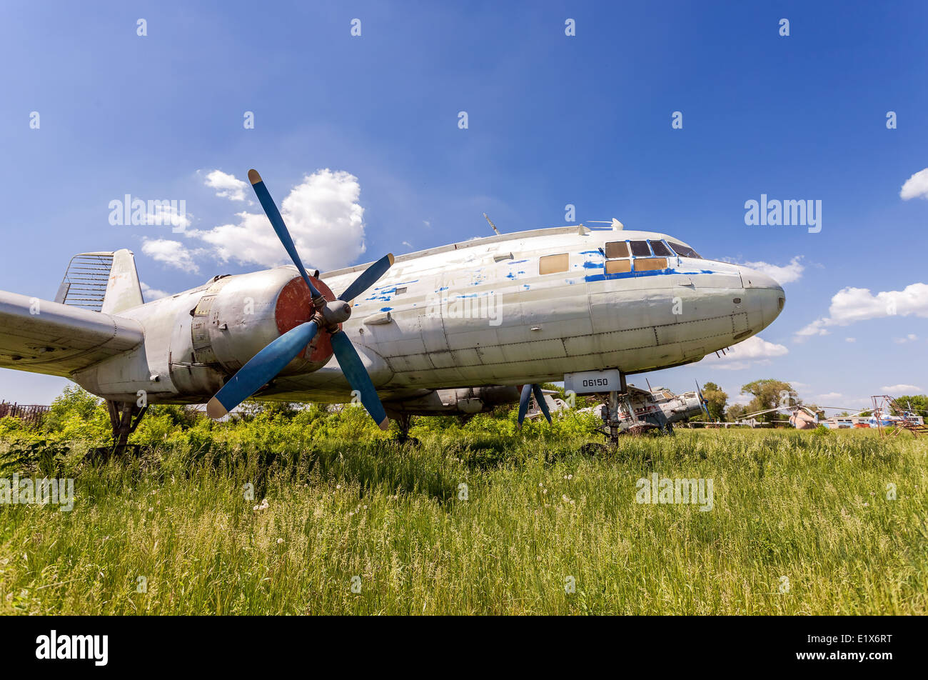 Old russian turboprop aircraft Il-14M at an abandoned aerodrome in summertime - Stock Image