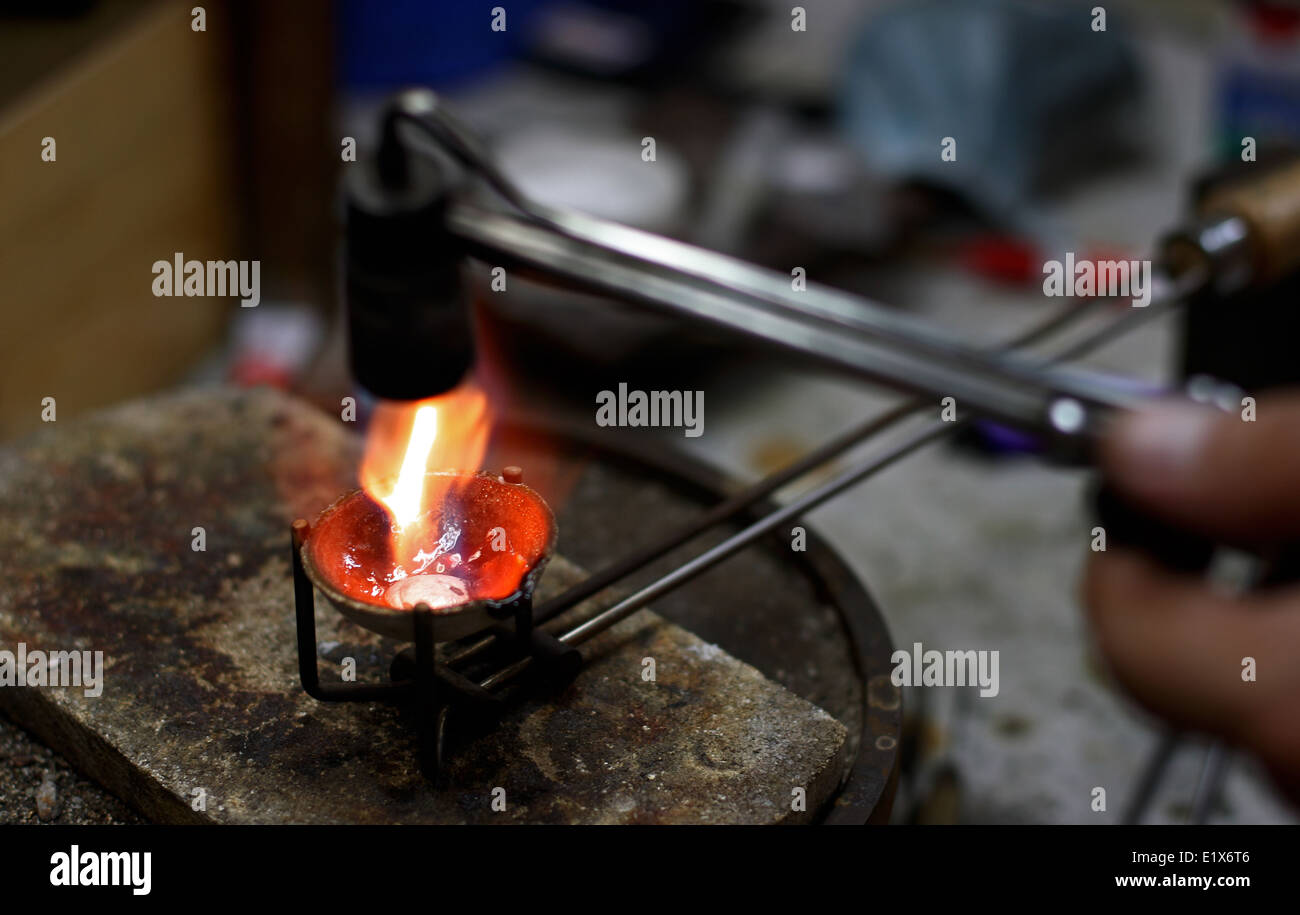 Melting silver in a small crucible for making jewelery. (Jeweller manufacture) - Stock Image