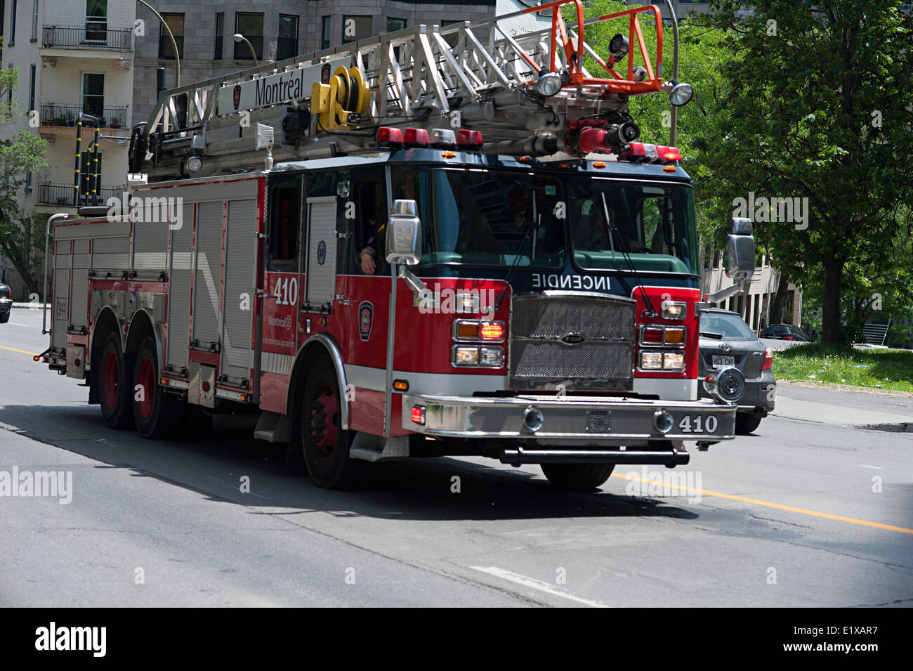 Fire engine races up a hill in Montreal, Quebec, Canada. - Stock Image
