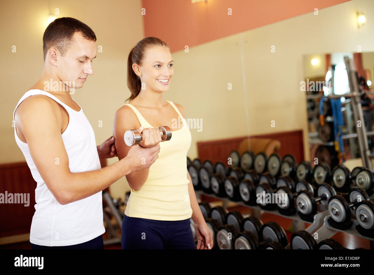Portrait of pretty girl training in gym with her trainer helping her - Stock Image