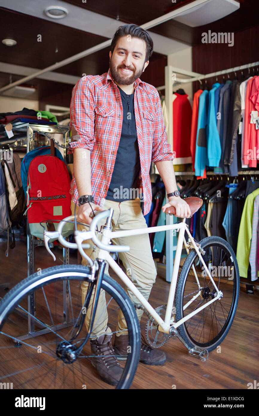 Portrait of a handsome man with bicycle looking at camera in sports shop Stock Photo