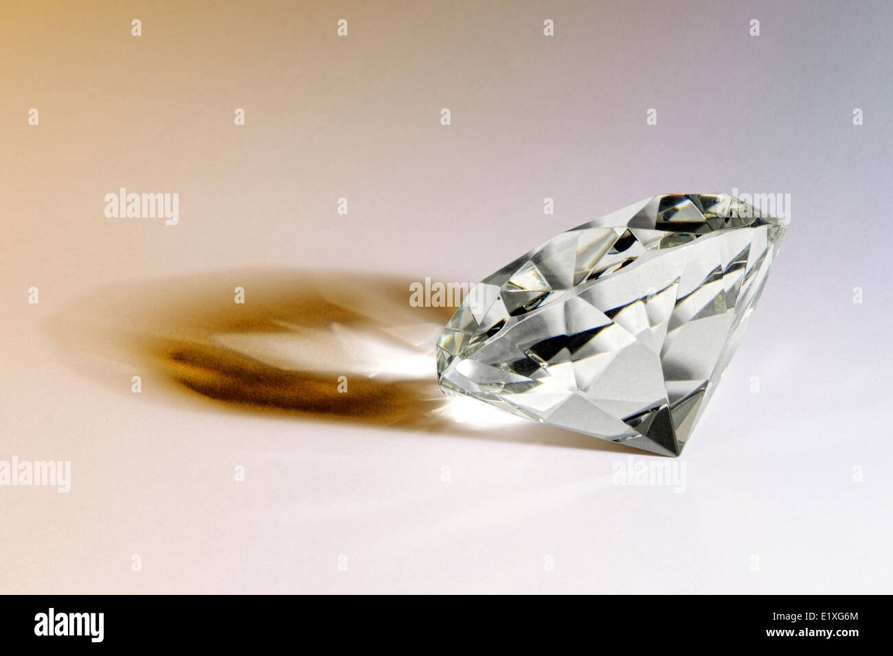 Faceted gemstone or diamond lying on its side on a white background casting an interesting shadow - Stock Image