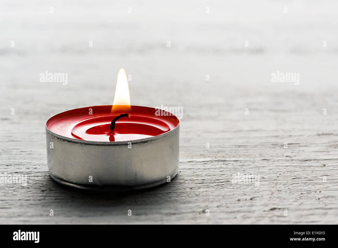 Single burning red tealight candle - Stock Image