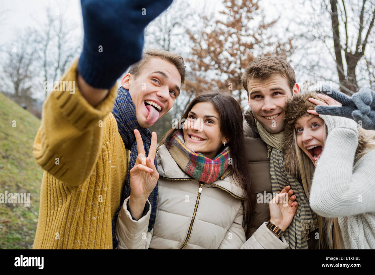 Playful couples gesturing while taking self portrait in park - Stock Image
