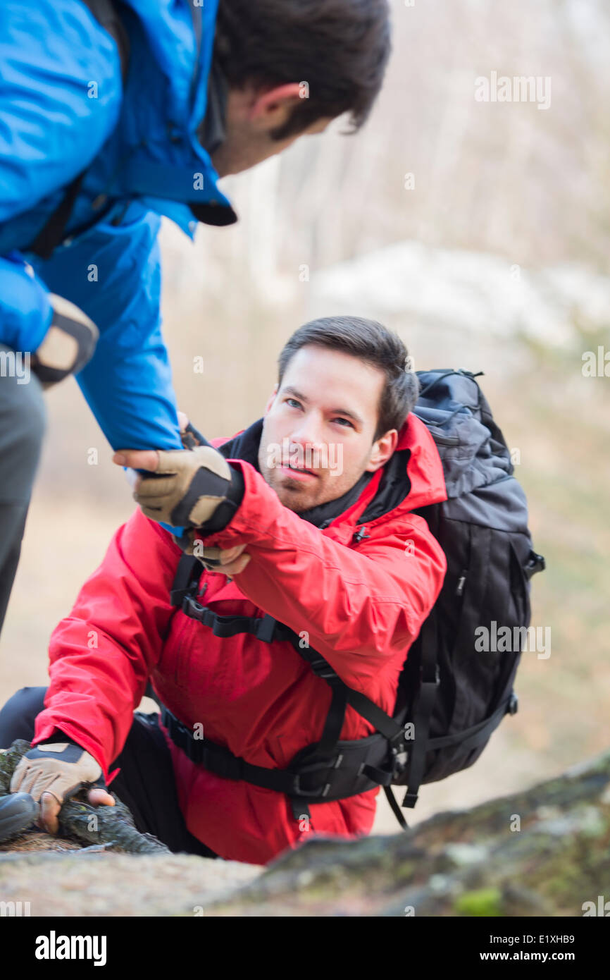 Male hiker helping friend while trekking in forest - Stock Image