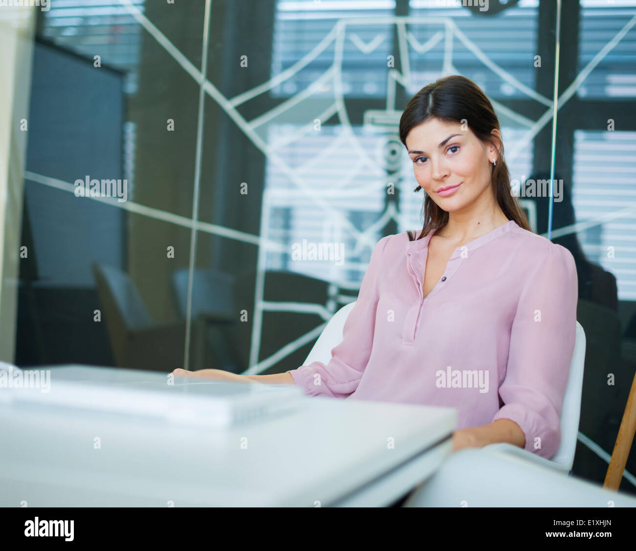 Portrait of confident young businesswoman at conference table - Stock Image
