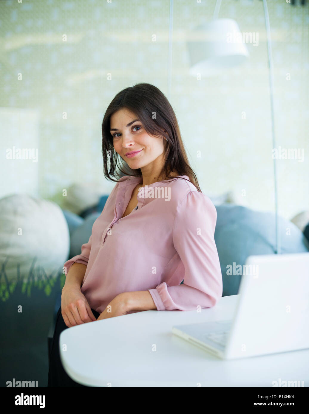 Portrait of confident young businesswoman leaning at office table - Stock Image