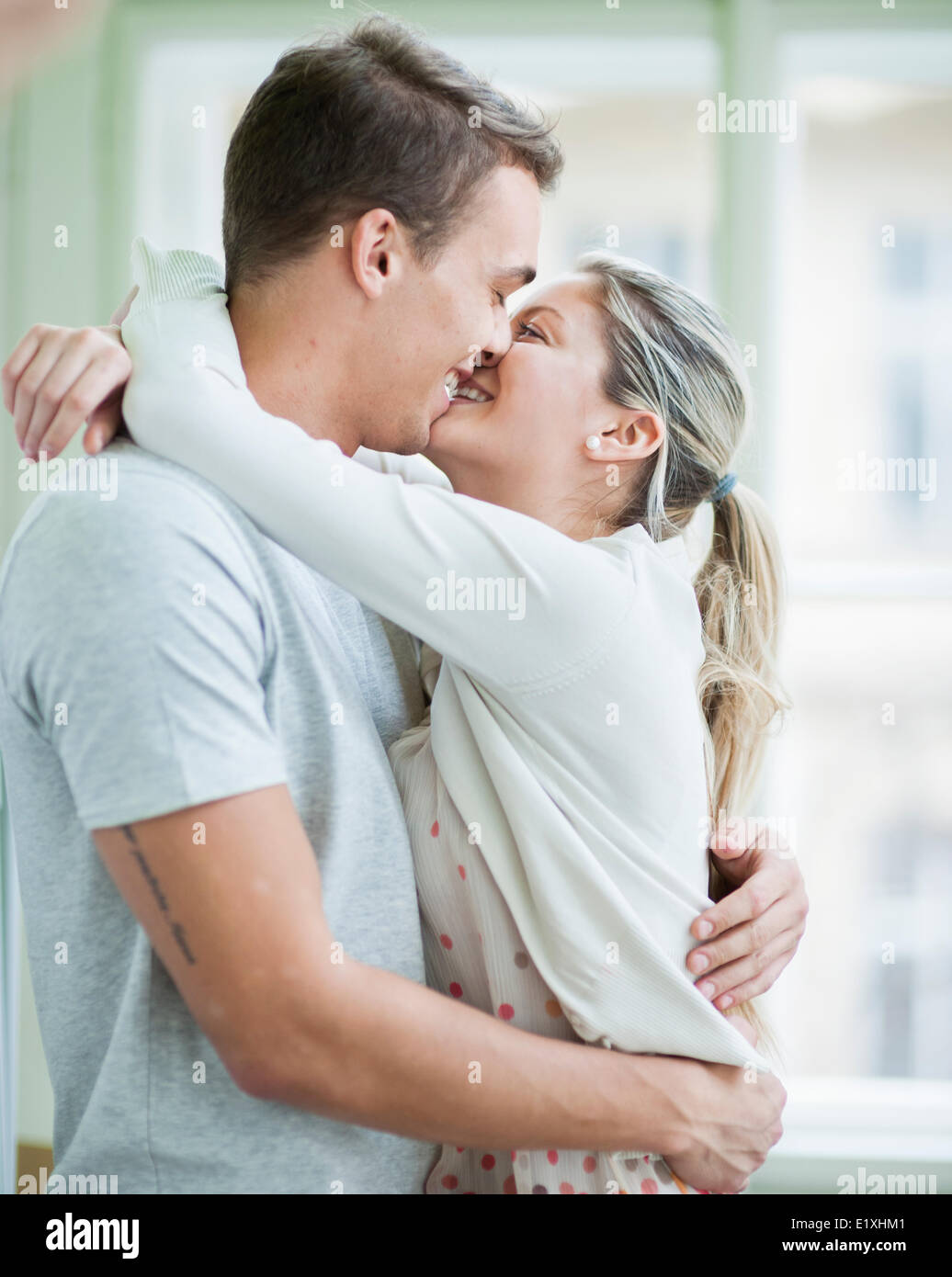 Loving couple kissing while hugging in house - Stock Image